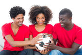Football fans in red holding ball together — Stock Photo