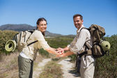 Hiking couple putting hands together on country trail — Stock Photo