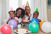 Happy family celebrating a birthday together at table — Zdjęcie stockowe