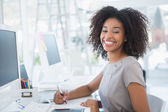 Young pretty designer smiling at camera at her desk — Stock Photo