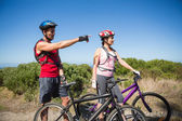Active couple cycling in the countryside looking ahead — Stock Photo
