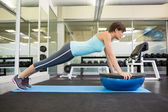 Fit brunette using bosu ball in plank position — Stock Photo