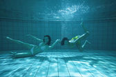 Pretty friends looking at camera underwater in bikinis — Stock Photo