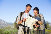 Hiking couple consulting the map in the countryside — Стоковое фото