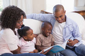 Happy family sitting on couch together reading book — Stock Photo