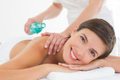 Attractive woman getting massage oil on her back — Stock Photo