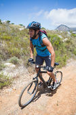 Man cycling up mountain trail — Stock fotografie
