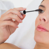 Hand applying mascara to beautiful woman — Stock Photo