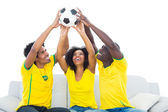 Happy football fans in yellow sitting on couch with ball — Stock Photo
