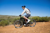 Fit cyclist riding on country terrain — Stock Photo