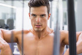 Determined shirtless young muscular man in gym — Stok fotoğraf