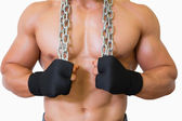 Mid section of a shirtless muscular man holding chain — Stock Photo