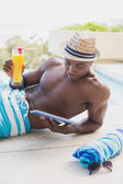 Handsome shirtless man using tablet pc poolside with cocktail — Stock Photo