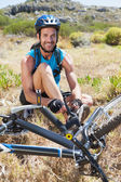 Fit cyclist tying his shoelace on mountain trail — Stock Photo