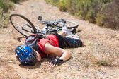 Injured cyclist lying on ground after a crash — Stock Photo
