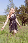 Pretty blonde in sundress walking through field — Stock Photo