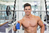 Smiling shirtless muscular man giving thumbs up in gym — Stock Photo