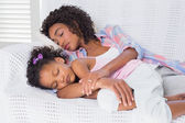 Cute daughter sleeping with mother on the sofa — Stock Photo
