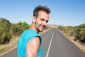 Fit man jogging on the open road smiling at camera — Stock Photo