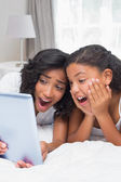 Surprised mother and daughter using tablet together — Stock Photo