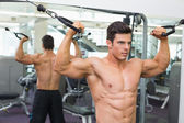Shirtless muscular man using resistance band in gym — Stock Photo