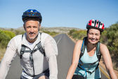 Active couple going for a bike ride in the countryside — Stok fotoğraf
