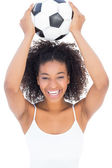 Pretty girl with afro hairstyle smiling at camera holding footba — Stock Photo