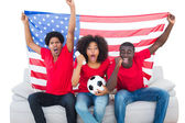 Cheering football fans in red sitting on couch with usa flag — Stock Photo