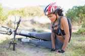 Fit woman lying on ground after bike crash — Stock Photo