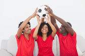 Football fans sitting on couch holding ball — Stock Photo
