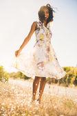 Mulher muito feliz que está na grama no vestido floral — Foto Stock