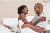 Happy couple sitting on bed cuddling — Stock Photo