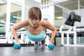 Fit brunette in plank position with dumbbells — Foto Stock