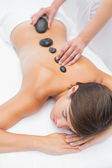 Beautiful woman receiving stone massage at spa center — Stock Photo