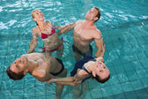 Happy fitness class stretching in aqua aerobics — Stock Photo