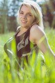 симпатичная блондинка в сарафане, сидя на траве — Стоковое фото