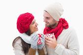 Atractiva joven pareja en ropa de abrigo celebración de tazas — Foto de Stock