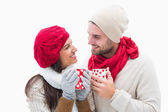 Attractive young couple in warm clothes holding mugs — Stock Photo