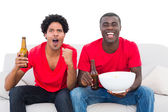 Football fans in red with beers and popcorn — Stock Photo