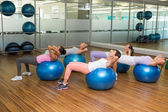Fitness class doing sit ups on exercise balls in studio — Stock Photo