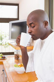 Happy man in bathrobe drinking coffee — Stock Photo