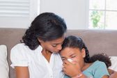 Concerned mother cuddling sick daughter — Stock Photo