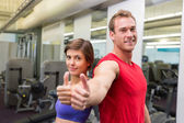 Fit attractive couple smiling at camera showing thumbs up — Stock fotografie