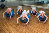 Fitness class stretching on exercise balls in studio — Stock Photo