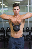 Muscular man lifting kettle bell in gym — Foto de Stock