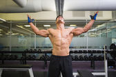 Bodybuilder with arms raised in gym — Stock Photo