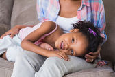 Cute daughter lying across mothers lap — Stockfoto