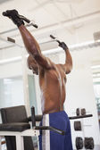 Male body builder doing pull ups at the gym — Stock Photo