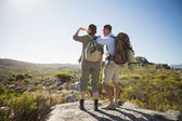 Hiking couple looking out over country terrain — Stock Photo