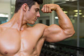 Muscular man flexing muscles in gym — Stock fotografie